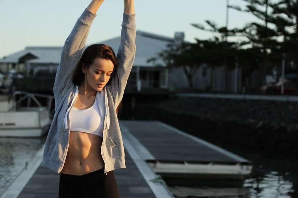 Junge Frau mit flachem Bauch nach dem Sport am Steg.