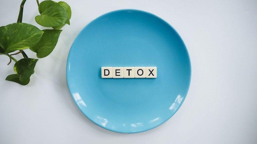 Ein blauer Teller mit dem Wort Detox darauf, daneben eine Pflanzen.