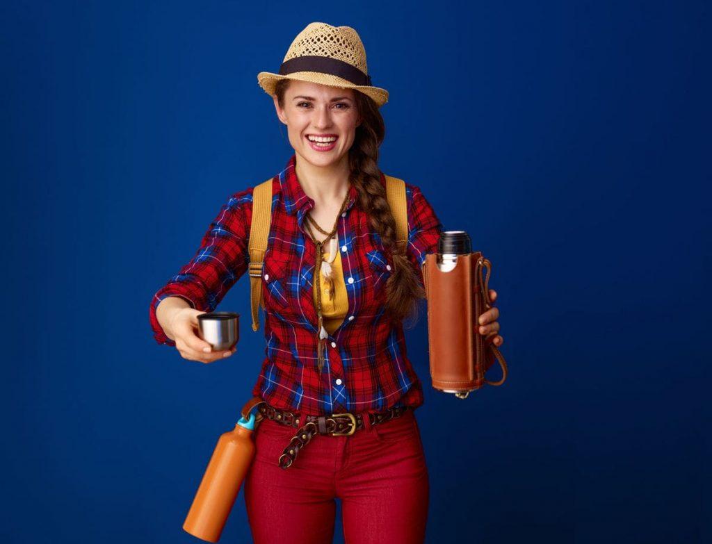 Junge Frau vor blauem Hintergrund mit Hut auf und zwei Thermoskanne in der Hand und am Gürtel befestigt.