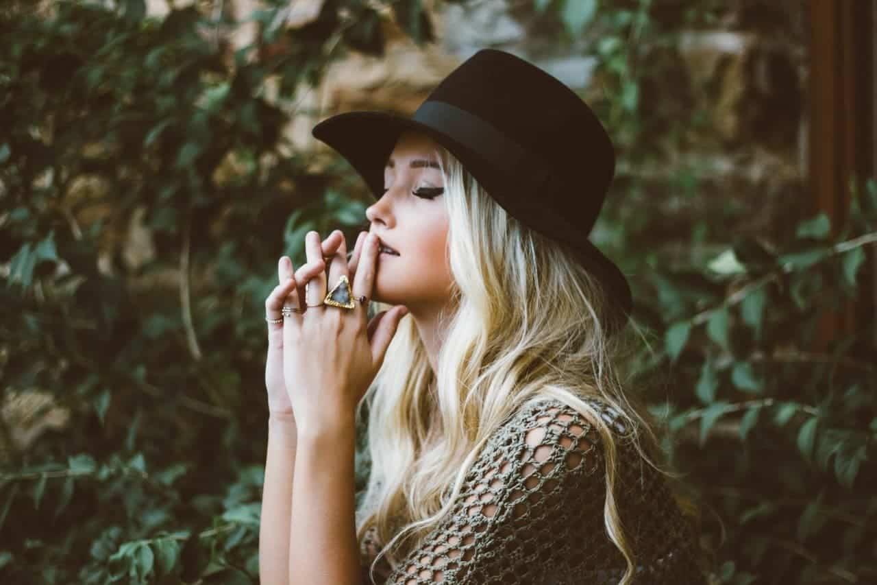Eine blonde schöne Frau mit Hut beim Manifestieren mit geschlossenen Augen.