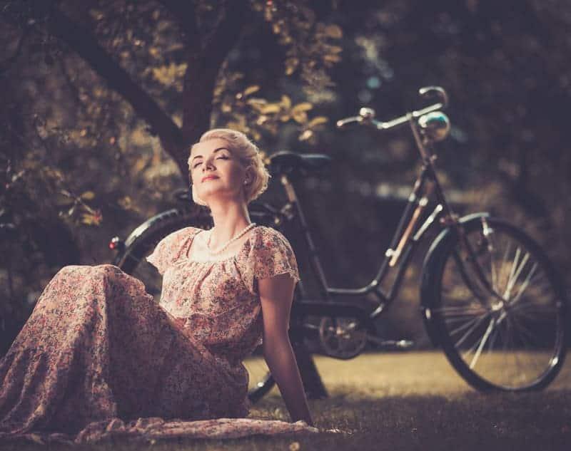 Eine Dame vor einen alten Fahrrad, in einem wunderschönen Kleid beim Manifestieren.