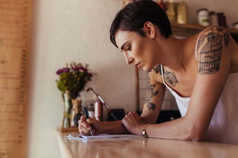 Frau mit kurzen Haaren schreibt ihre Wünsche auf.